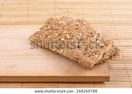 Crispbread with a variety of seeds on the board. - stock photo
