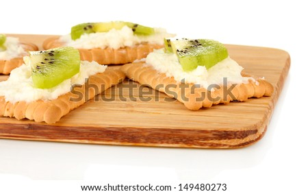 Crispbread with cheese and kiwi, on cutting board, isolated on white