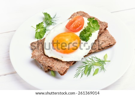 Crispbread with egg, tomato slice and herbs, close up view - stock photo