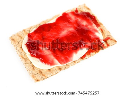 crispbread with red jam and white background