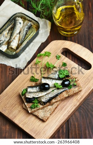 Crispbread with sprats and olives on wooden cutting board - stock photo
