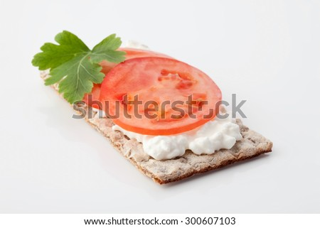 Crispbread with tomato slice,parsley and cream cheese