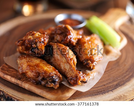 crispy barbcue chicken wings with celery on wooden serving tray - stock photo