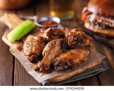 crispy barbecue chicken wings with celery on wooden serving tray - stock photo
