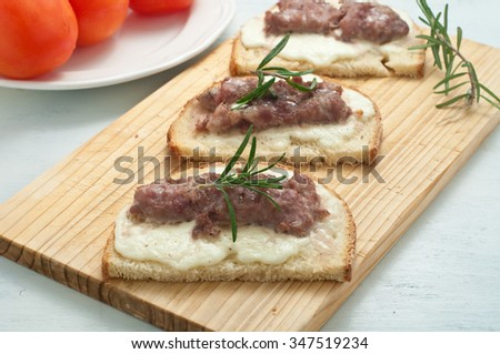 Crispy bruschetta topped with sausage and fresh rosemary,italy - stock photo
