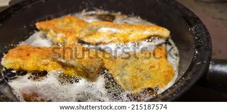 Crispy carp fillet during frying for Christmas dinner in Czech Republic - stock photo