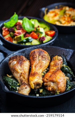 Crispy chicken legs on spinach with avocado salad - stock photo