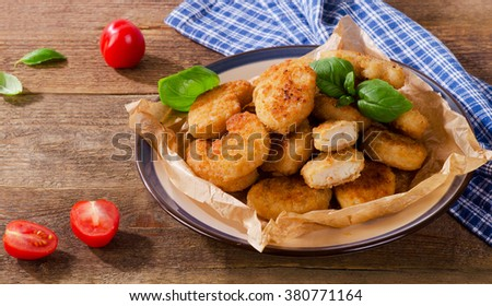 Crispy chicken nuggets on a rustic wooden background. Selective focus - stock photo