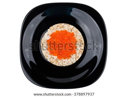 Crispy corn bread with red caviar in black plate isolated on white background, top view