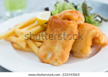 Crispy fish and chips with sliced lemon and vegetable
