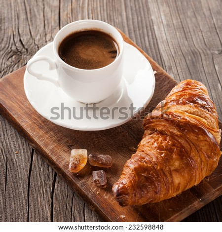 Crispy fresh croissant and cup of coffee on a dark wooden background, selective focus