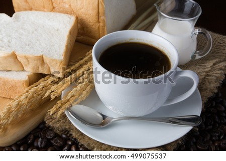 Crispy fresh croissants and cup of coffee espresso on a rustic wooden background