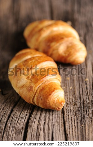 Crispy fresh croissants on a wooden table