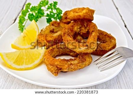 Crispy fried calamari rings on a plate with slices of lemon and parsley on a wooden boards background
