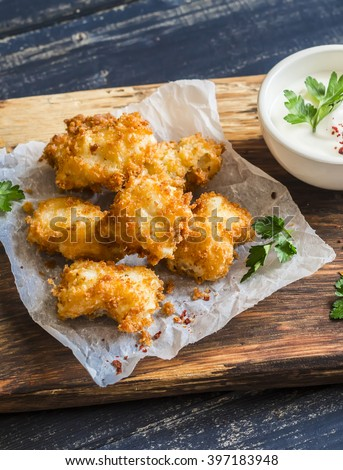 Crispy fried fish on a wooden rustic board - stock photo