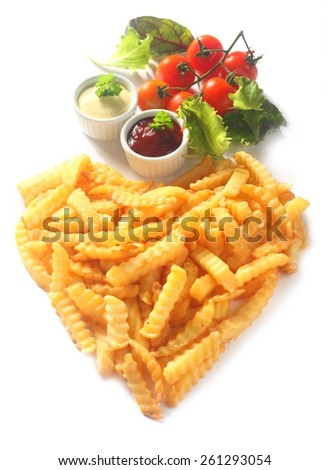 Crispy golden crinkle cut French fries arranged in a heart shape symbolic of love, romance or Valentines Day with with dips, tomatoes herbs and lettuce, high angle on white - stock photo