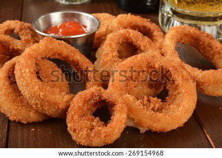 Crispy golden onion rings with a mug of beer - stock photo