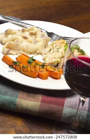 Crispy Greek yogurt baked chicken with roasted carrots home style mashed potatoes and a glass of red wine - stock photo