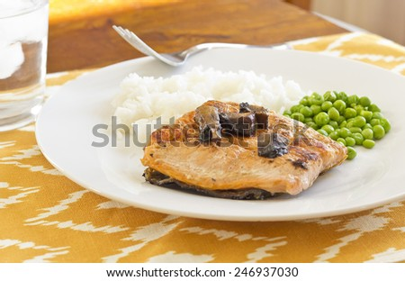 Crispy grilled salmon fillet with roasted portobello mushrooms and sweet glaze with peas and rice on the side - stock photo