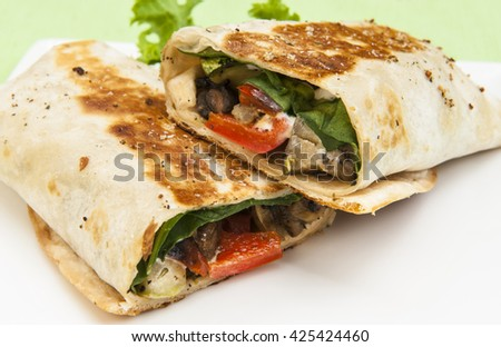 Crispy grilled vegetable wrap on a white plate