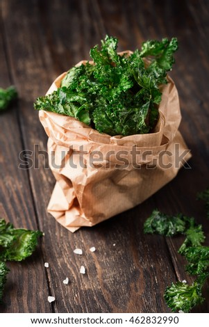Crispy Homemade Baked Kale Chips with Olive Oil and Sea Salt on rustic wooden background, selective focus