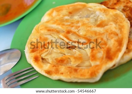 Crispy Indian roti prata cuisine with curry side dish. For diet and nutrition, healthy lifestyle, and Asian cuisine concepts. - stock photo