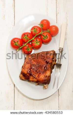 crispy marinated ribs with meat fork and fresh tomatoes on an oval plate