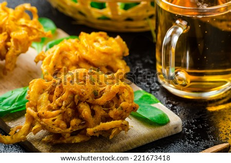 Crispy Onion Bhajis with creame cheese dip with jalapeno and crunchi toast on spinach leaves and czech beer - stock photo
