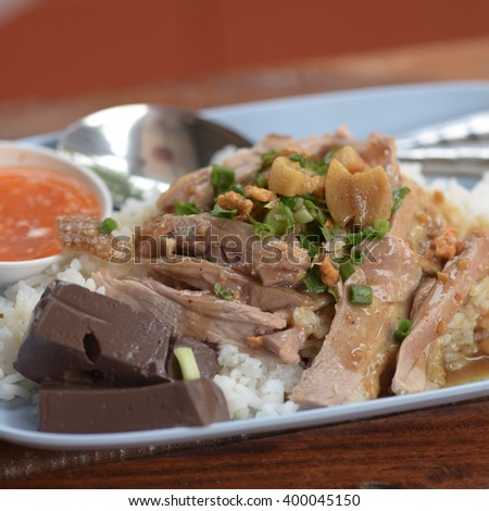 Crispy Pork and roast duck with BBQ sauce top on rice.