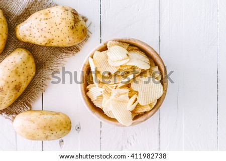 Crispy potato chips in a wooden bowl on wooden table - stock photo