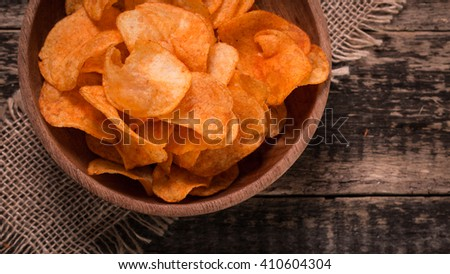 Crispy potato chips in bowl on wooden background - stock photo