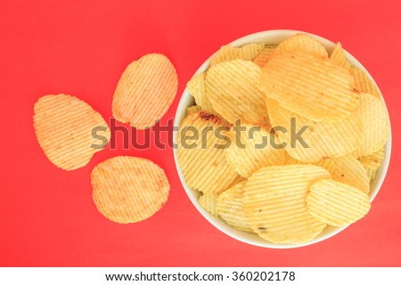 crispy potato chips junk food unhealthy food on bowl red background - stock photo