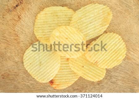 crispy potato chips junk food unhealthy food on wooden - stock photo