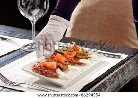 Crispy potato pancakes decorated with salmon and sour cream being served by a waiter