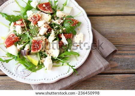 Crispy salad with arugula, sliced �¢??�¢??pears and figs on a white plate, food closeup - stock photo