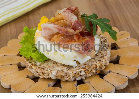 Crispy sandwich with egg, bacon and salad leaves - stock photo