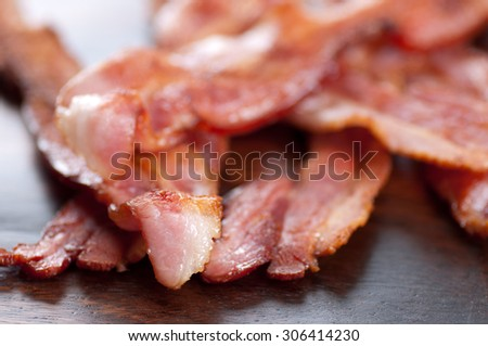 crispy sliced ethically raised organic bacon on a wooden plate - stock photo