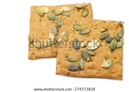 crispy spelt crackers with pumpkin seeds on a white background - stock photo