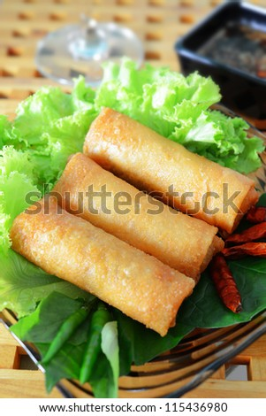 crispy spring rolls on clear dish with vegetable - stock photo