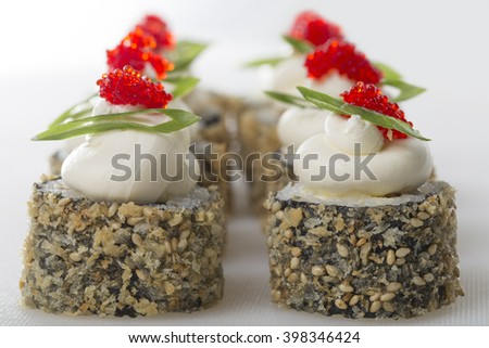 Crispy sushi roll with tobiko caviar and japanese mayonnaise on top. Macro. On a table as a background. - stock photo