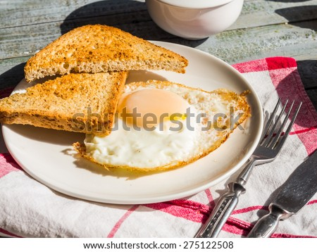 crispy toast with a fried egg and a cup of coffee. breakfast on the wooden background