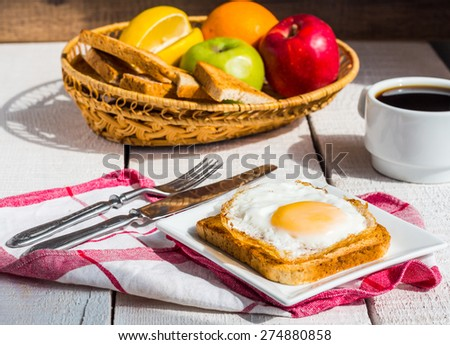 crispy toast with a fried egg and a cup of coffee, fruit, breakfast on the wooden background - stock photo