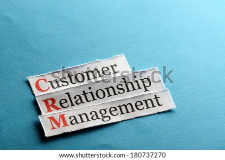 CRM customer relation management abbreviation on blue paper - stock photo