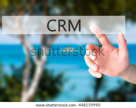 CRM - Hand pressing a button on blurred background concept . Business, technology, internet concept. Stock Photo