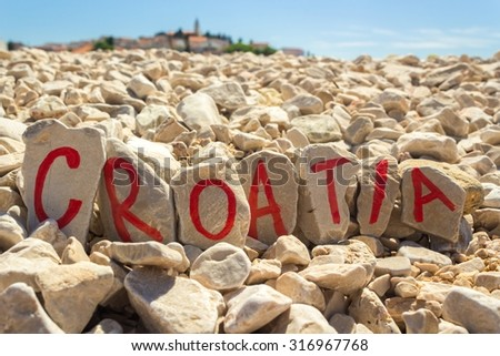 Croatia text painted on stones beach with dalmatian town in the background