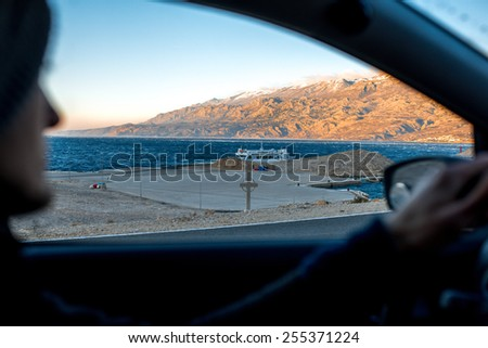 Croatian coasts with ferry floating on the sunset. View from the car with man driving - stock photo