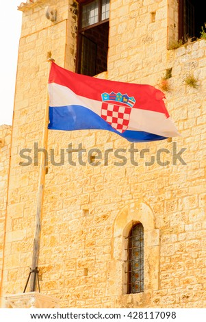 Croatian flag on the Cathedral of St. Lawrence (Katedrala Sv. Lovre), a Roman Catholic triple-naved basilica constructed in Romanesque-Gothic in Trogir, Croatia. UNESCO World heritage - stock photo