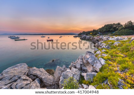 Croatian rocky coast resort. Long exposure image of tourism, rocks, vegetation, and boats on the Island of Cres in the adriatic sea. - stock photo