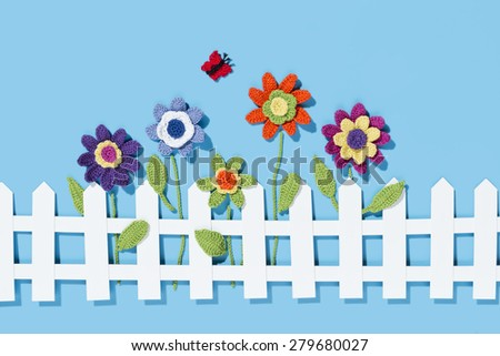 crochet flowers behind a white paper fence with a butterfly on blue background