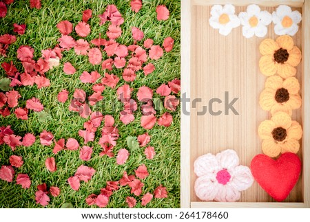 Crochet flowers in a wooden frame with heart on the grass. - stock photo
